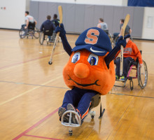Otto the Orange in a wheelchair raising hands in the air cheering