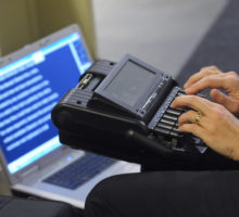 Person's hands using an assistive technology device