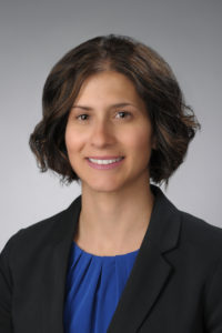 Melanie Domanico is shown from the chest up, facing the camera, with her body slightly angled towards the left. She is wearing a black suit jacket with a royal blue pleated shirt underneath. There is a grey background