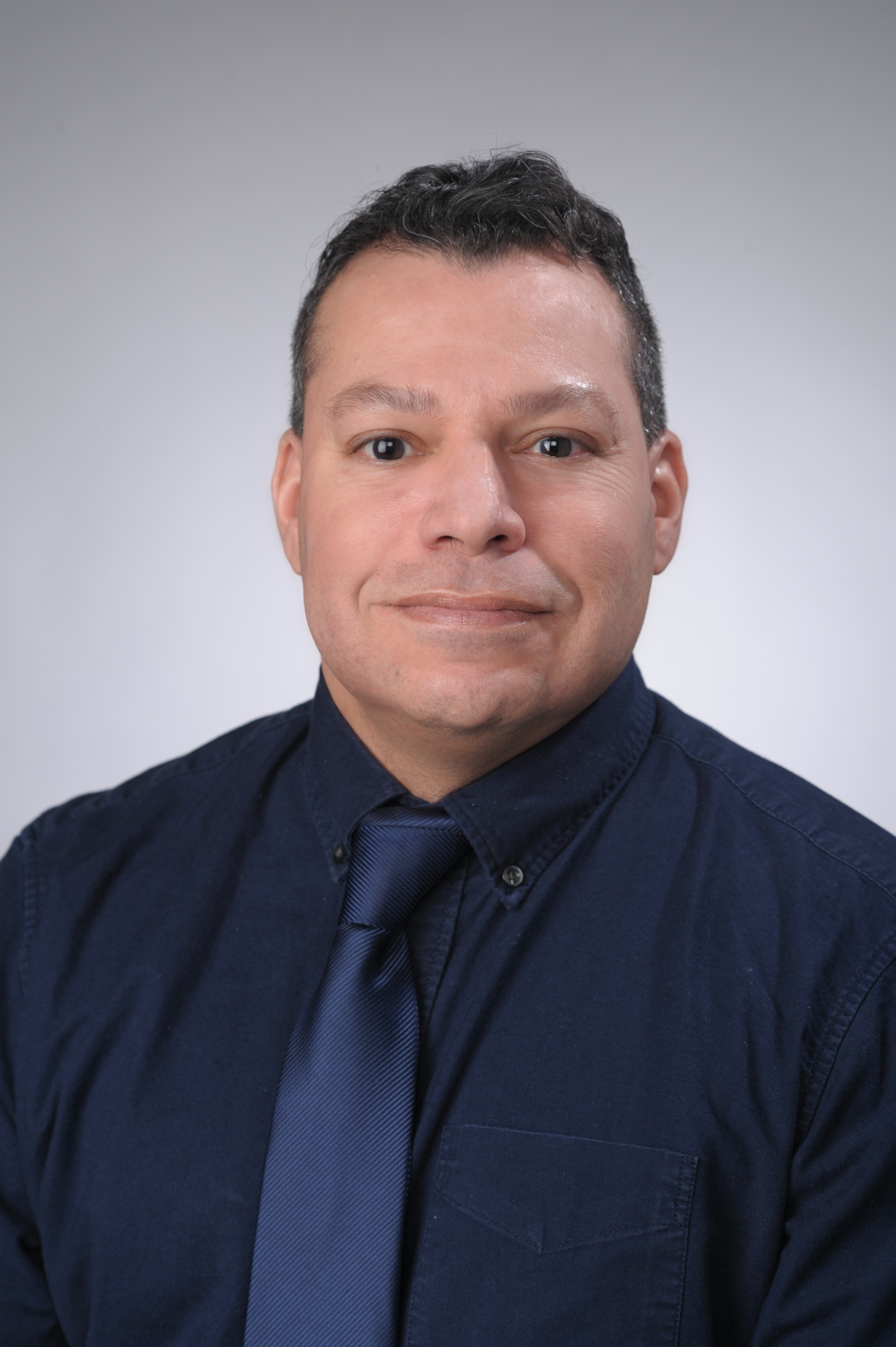 Patricio Jimenez is shown from the chest up, facing the camera, with his body slightly angled towards the right. He is wearing a blue dress shirt with a blue tie. There is a grey background