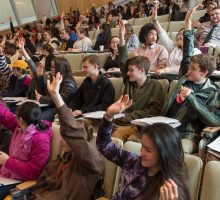 Photo of classroom with diverse group of students raising hands to answer question